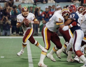 FILE - In this Jan. 26, 1992, file photo, Washington Redskins' Don Warren (85) keeps Buffalo Bills Cornelius Bennet (97) away from Redskins quarterback Mark Rypien during NFL football's Super Bowl XXVI in Minneapolis. Rypien passed for 292 yards and two touchdowns to lead the Redskins to their third Super Bowl title. (AP Photo/Jim Mone, File)